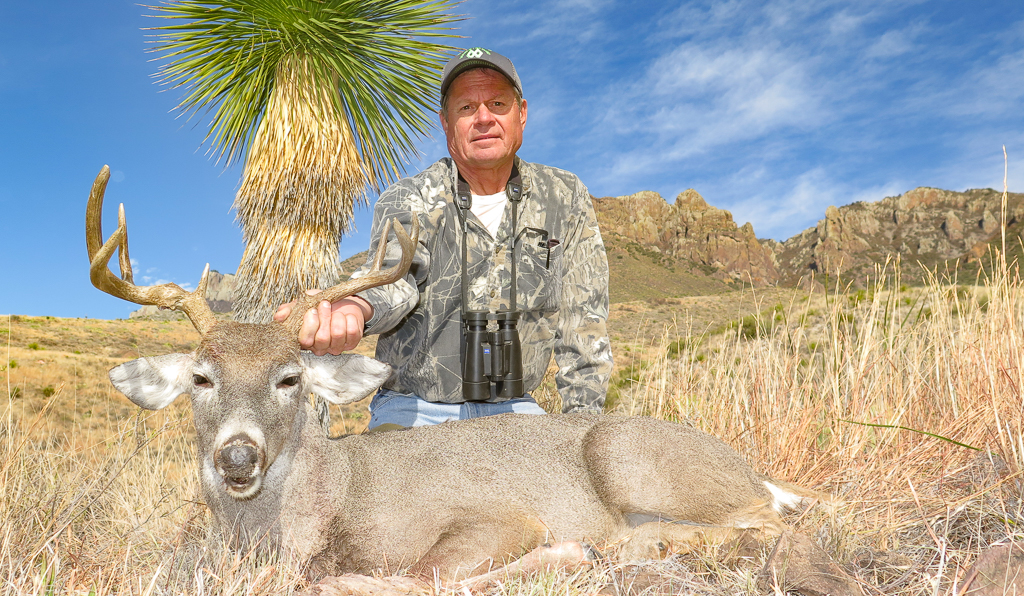 Hunter holding large Carmen Mountain Deer in front of Mexican Desert landscape
