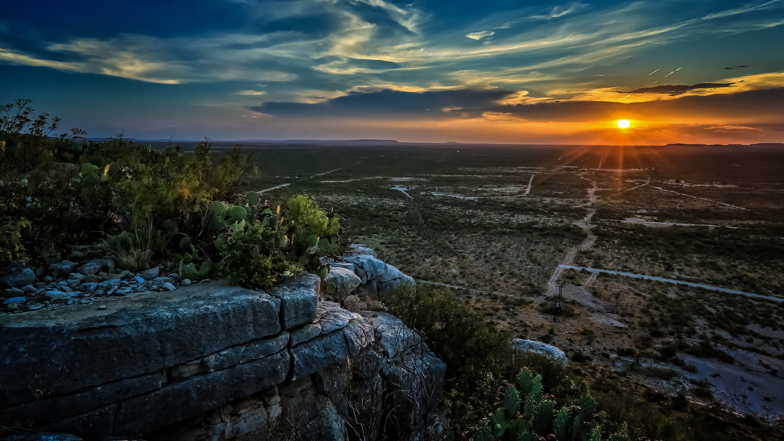 Sunrise in the mountains of West Texas with rocks in the foreground and flat open space in distance with the sun rising at the horizon