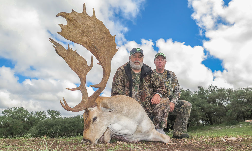 Two hunters posing with a spotted Fallow Deer