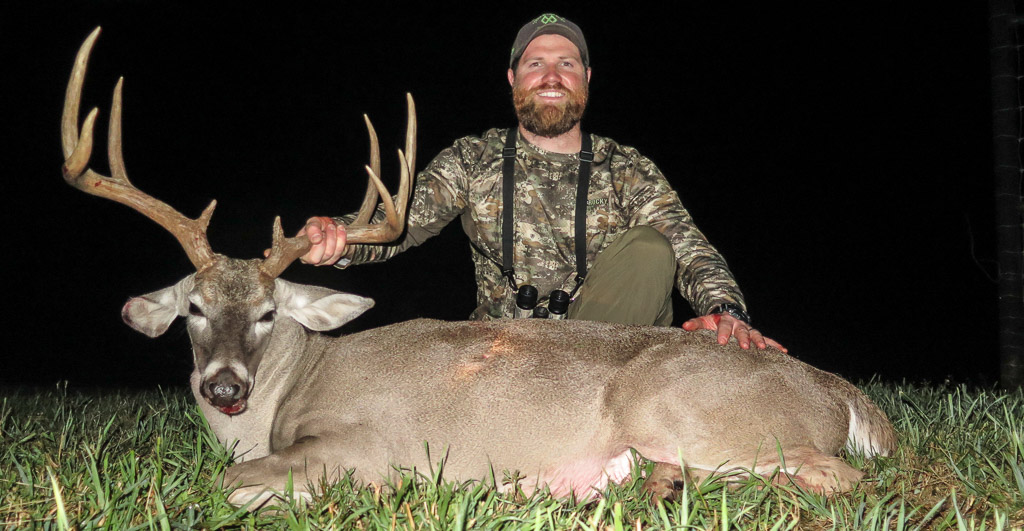 Hunter posing with large Whitetail buck at night