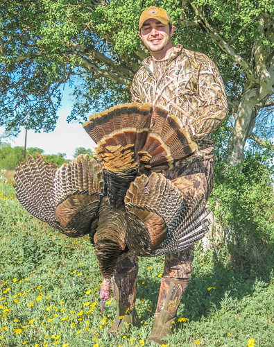 Hunter holding large Texas Turkey while standing next to a tree