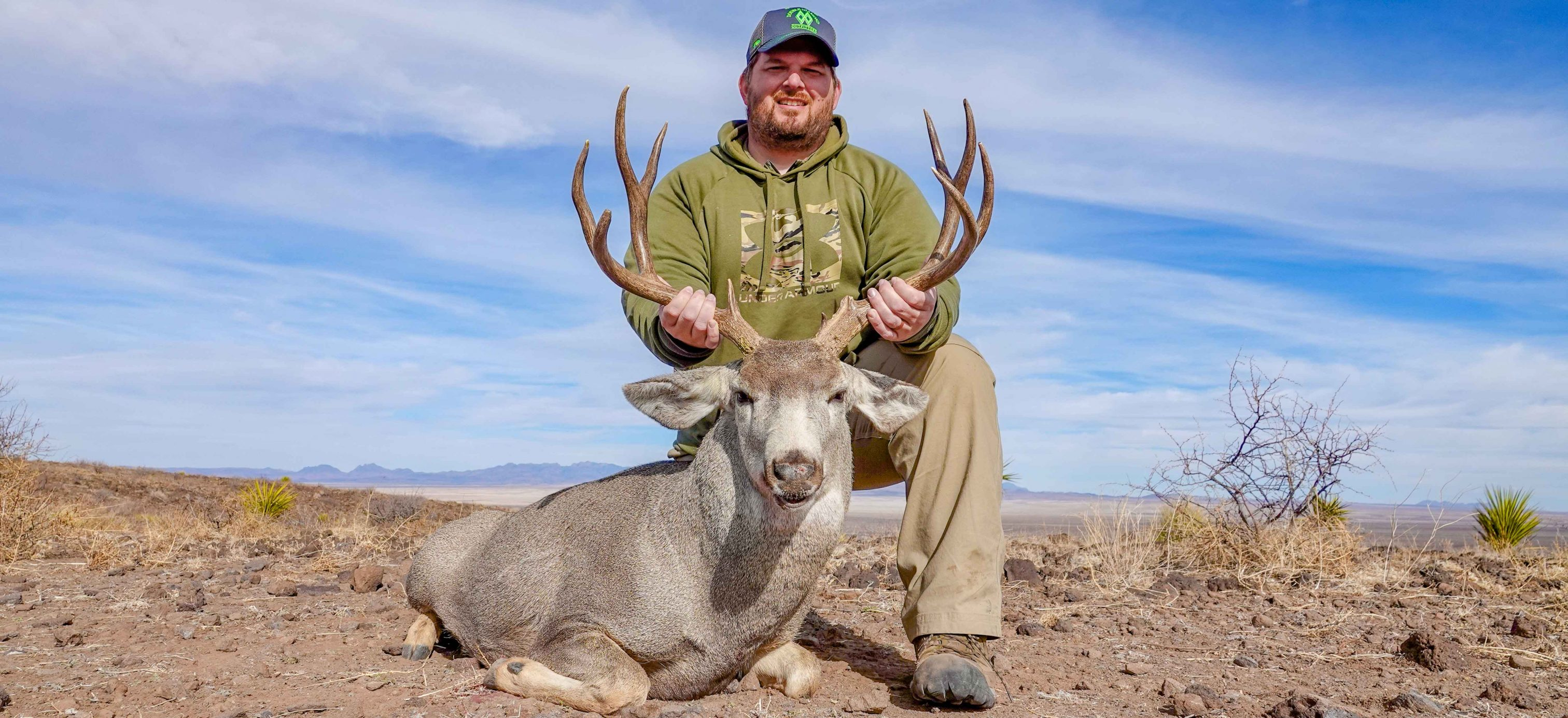 Hunter holding head of large Texas Mule Deer after Texas Mule Deer Hunt with Hunt Double Diamond Outfitters